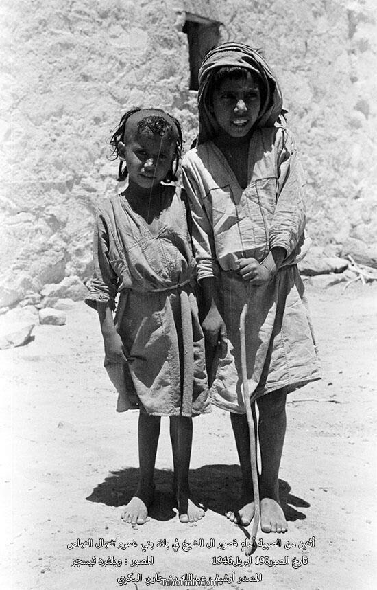 أثنين من الصبيه أمام قصور آل الشيخ في بلاد بني عمرو شمال النماص التقطت الصورة  في عام 1946م - أرشيف بن جاري