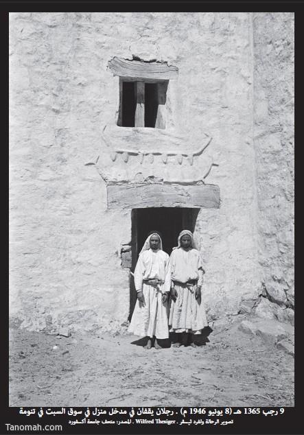 رجلان يقفان في مدخل منزل في سوق السبت في تنومة تصوير ولفرد ثيسقر  في 9 رجب 1365هـ