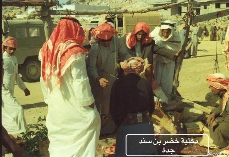 بعض المتسوقين في سوق شعبي بالنماص يوزنون اللحم من أحد الجزارين