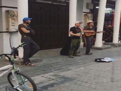 سائحان يقدمان عرضاً غنائياً في شارع بجدة التاريخية ويطلبان دعمهما بالمال